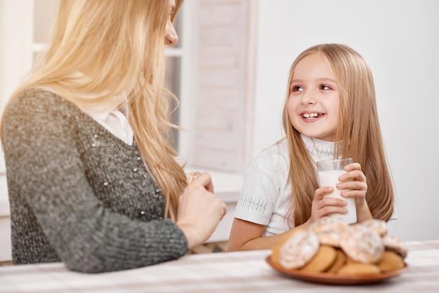 Улыбающаяся маленькая дочь сидит, держа стакан молока рядом с матерью