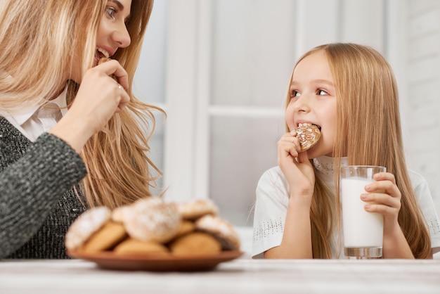 Мать и дочь едят печенье и улыбка