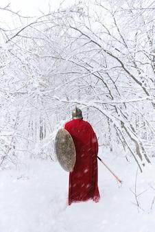 スパルタの戦士は長い赤いマントで冬の森を歩く