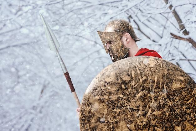 一人の質素な戦士が森に鎧を置いている