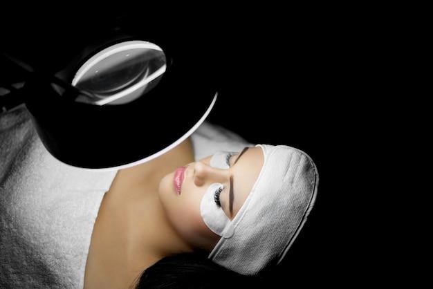 Клиент, лежащий под лампой во время увеличения ресниц