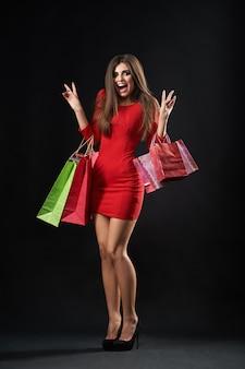 幸せな若い女性が買い物袋でポーズ