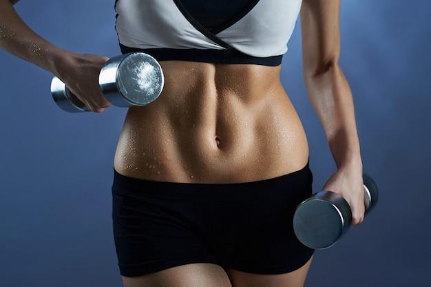 Женщина, носящая разминку, держащая веса
