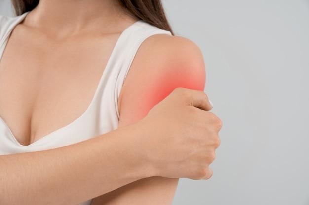 Женщина показывает боль в плече