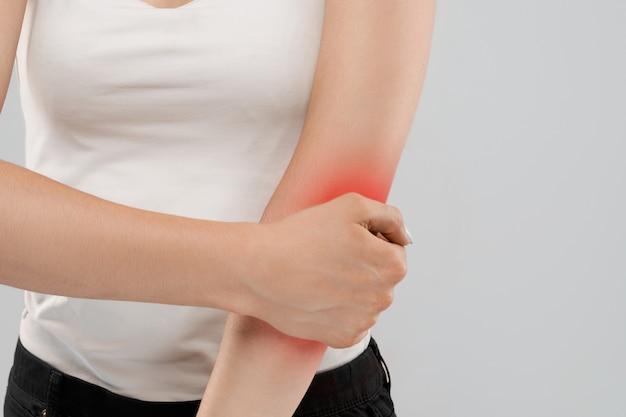 Женщина страдает от боли в локте