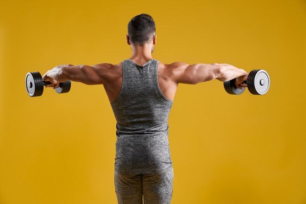 Мускулистый сильный мужчина делает упражнения с гантелями