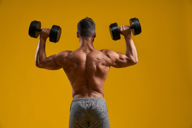 Сильный спортивный парень делает упражнения с гантелями