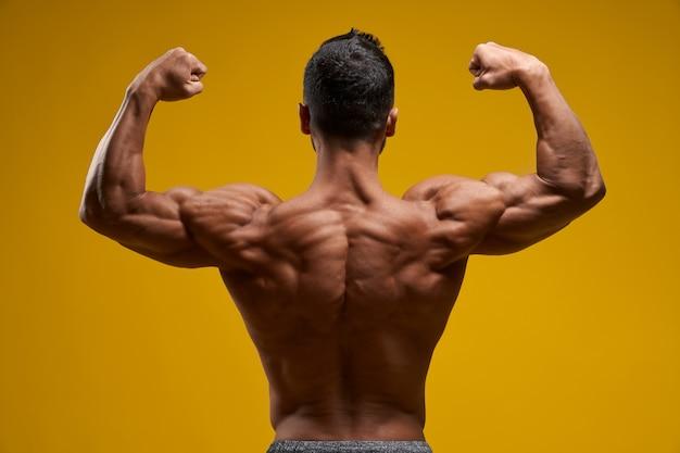 筋肉の腕と肩を示す上半身裸の男
