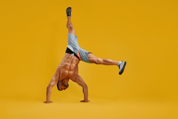 Сильный молодой человек делает упражнение стойку на руках