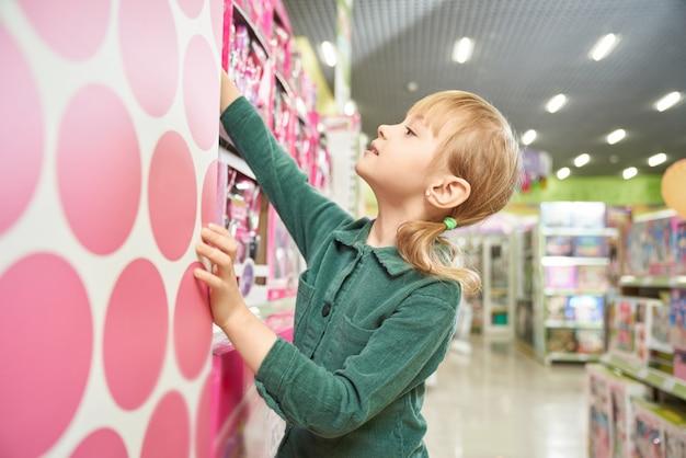 大きな店で自分からおもちゃを取っているかわいい女の子。