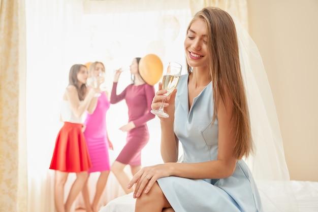 Невеста с бокалом шампанского, сидя на кровати.