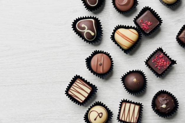 Вид сверху различных шоколадных конфет на деревянных фоне