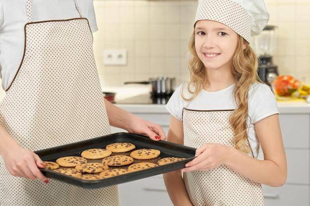 Девушка в приготовлении шляпу и фартук с подносом с печеньем