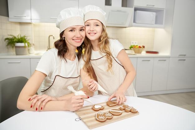 Женщина и ребенок украшения имбирное печенье, позирует.