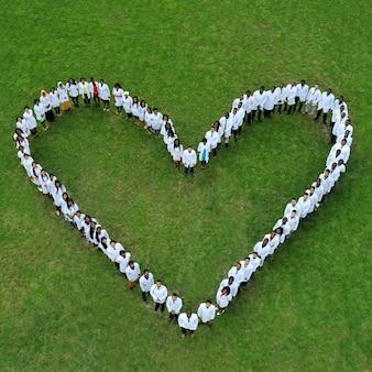 若い医学生が地面に立って、大きなチャリティーハートを作ります。