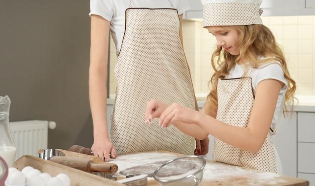 Милая девушка в фартук посыпать муки на шоколадное тесто.