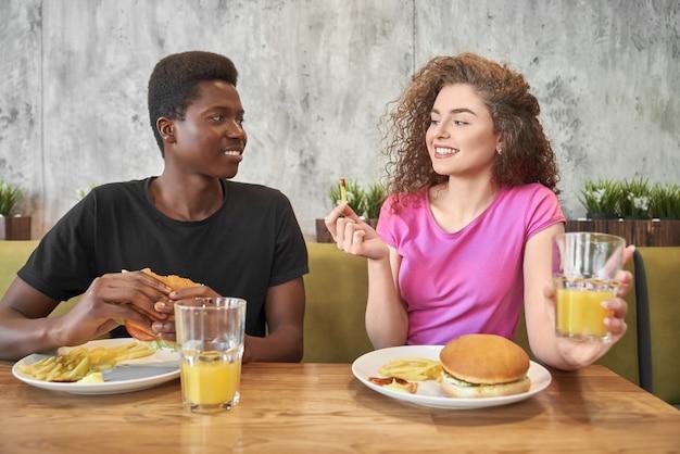 若い女性とハンバーガー、カフェでフライドポテトを食べる男。