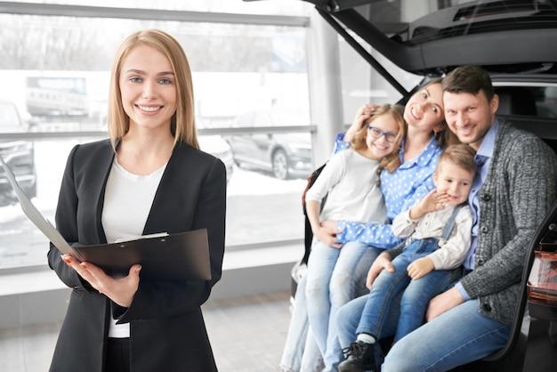 車のディーラーのマネージャーとポーズ、笑顔の幸せな家族。