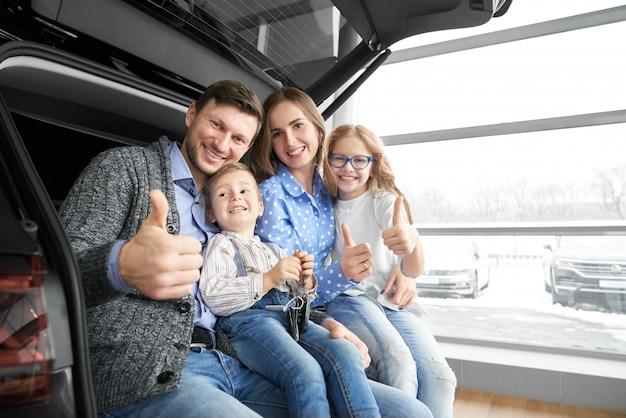 車のトランクでポーズをとって、親指を現して幸せな家族。