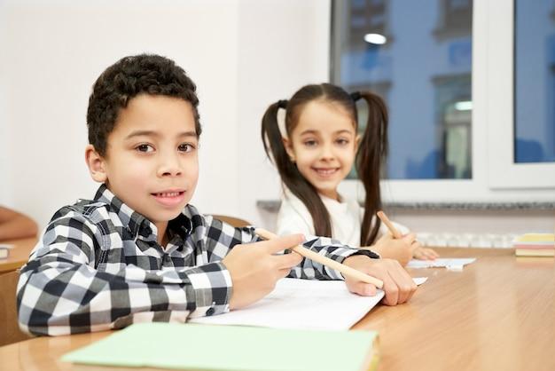 男の子と女の子が教室の机に座って、ポーズします。