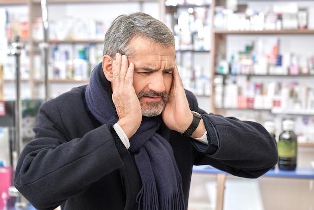 Человек, имеющий головную боль, хватая голову, стоя в аптеке.