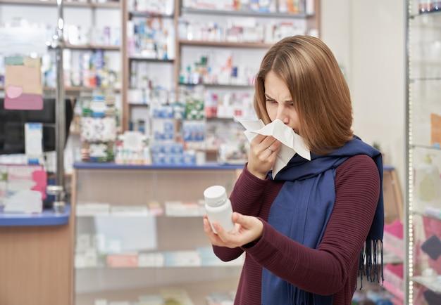 Женщина используя ткань в аптеке и держа бутылку пилюлек.