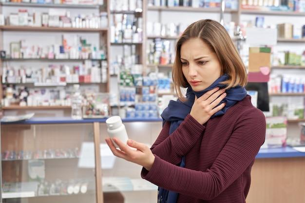 Клиент держит бот-макет с лекарствами в аптеке.