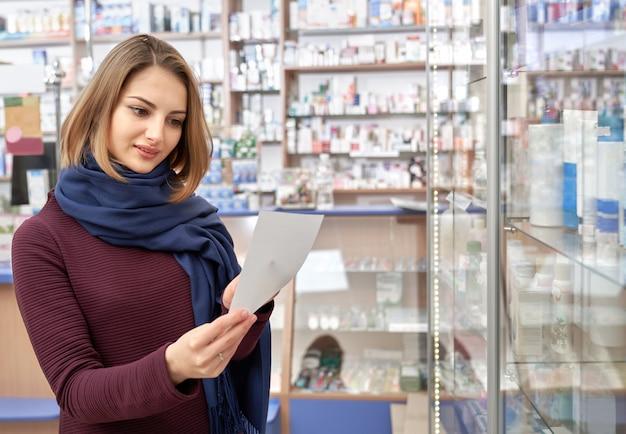 Красивая женщина, глядя на рецепт в аптеке.
