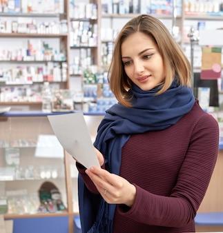 Рецепт чтения молодой женщины в магазине аптеки.