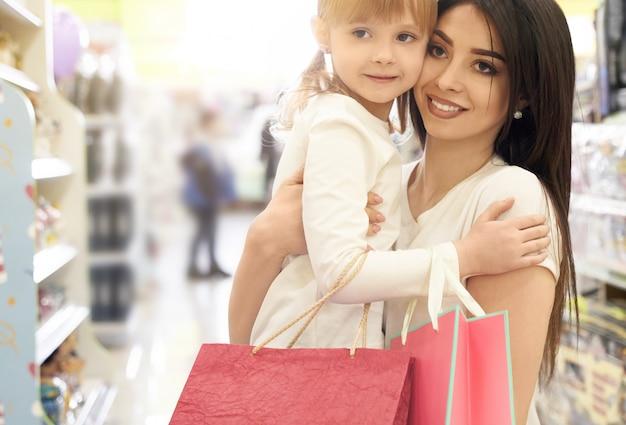 若い母親と娘がショッピングセンターでポーズします。