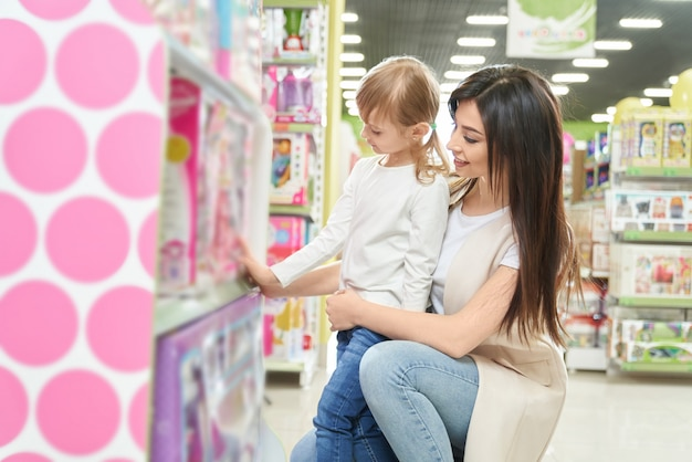 ショップで小さな娘と人形を選ぶ若い母親