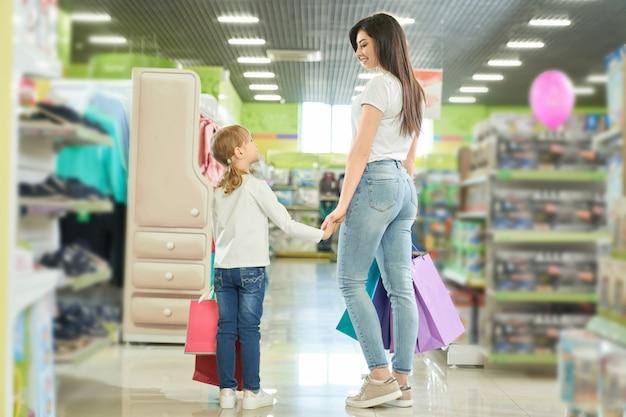 モールで買い物をしている母と娘の後ろからの眺め