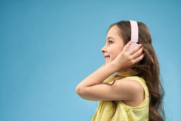 音楽を楽しむヘッドフォンで肯定的な女の子の側面図