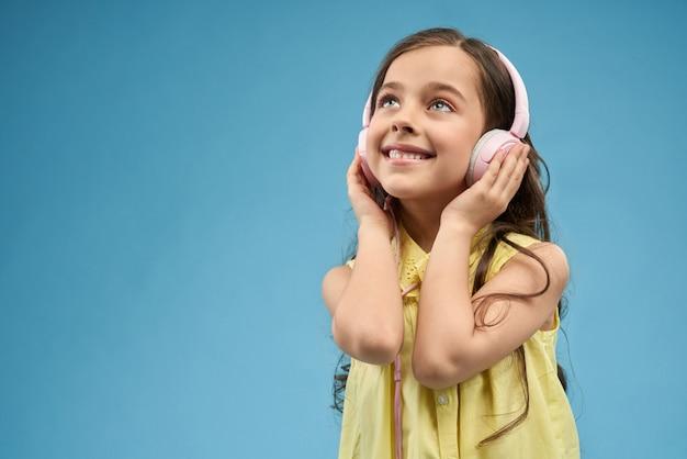 ピンクのヘッドフォンで音楽を聴く少女。