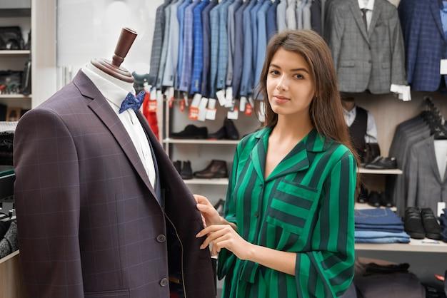 Женский консультант позирует с мужской пиджак, работает в магазине.