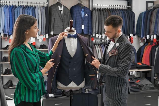 Консультант магазина и человек, выбирая костюм, глядя на манекен.