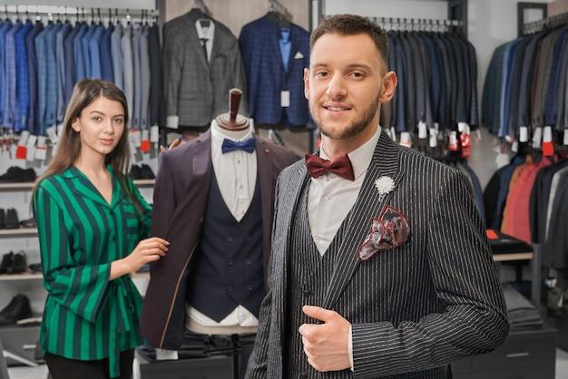 Молодой, стильный мужчина в элегантном костюме позирует в магазине.