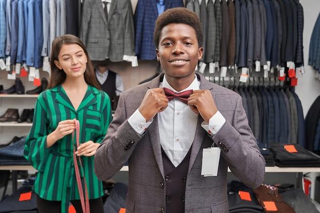 Клиент одевает белую рубашку, жилет и пиджак, красный галстук-бабочку.