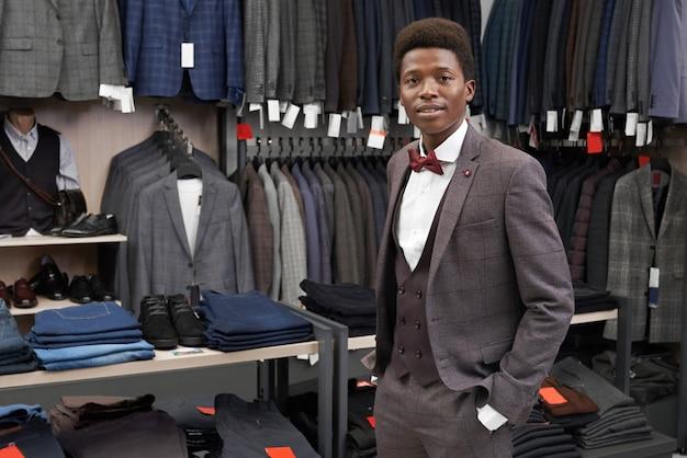 Клиент, держа руку в карман брюк, позирует в магазине.