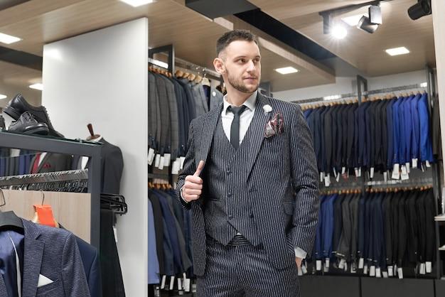Джентльмен позирует в костюме в выставочном зале бутика.