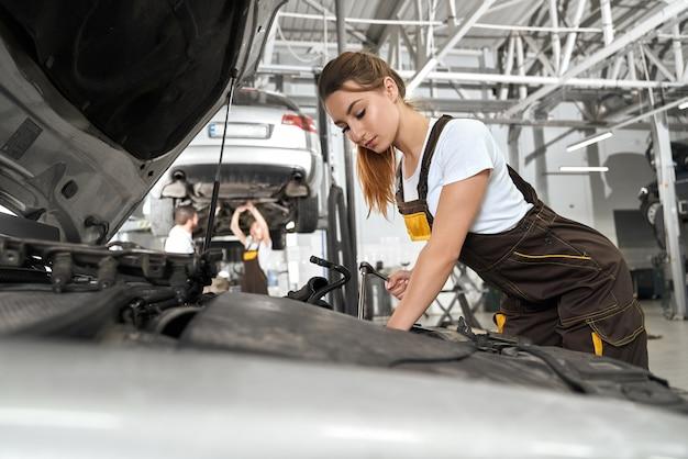 白いシャツとカバーオール修理エンジンの女性メカニック
