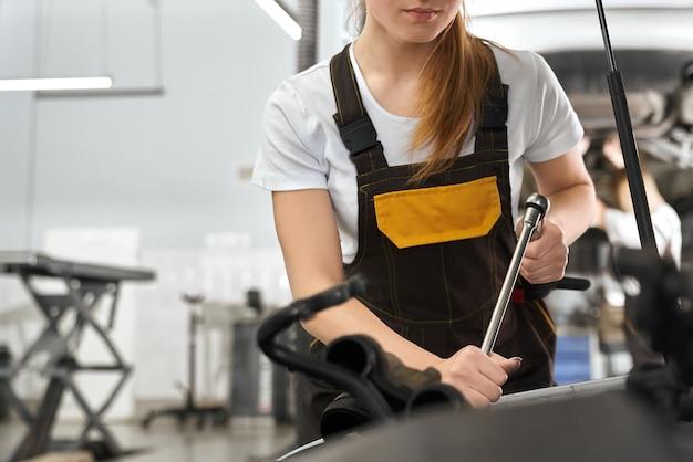 オートサービスで働くつなぎ服のきれいな女性