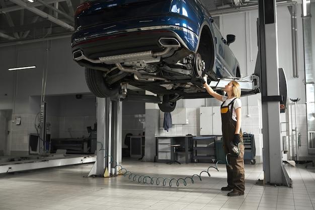Женщина-механик наблюдает за ходовой частью поднятой машины.
