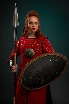 Серьезный женский рыцарь позирует с щитом и копьем.