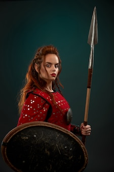 Средневековая женщина-воин позирует с копьем, щитом.