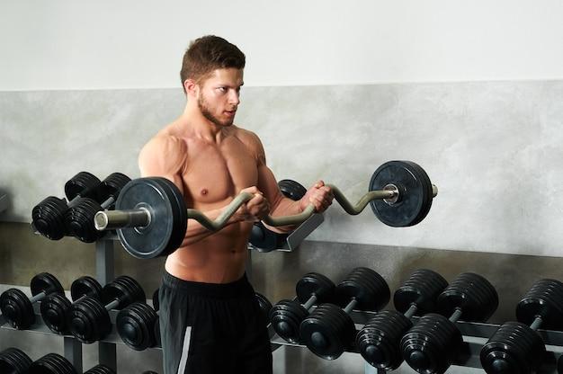 ジムで上腕二頭筋を行う若い筋肉質の選手