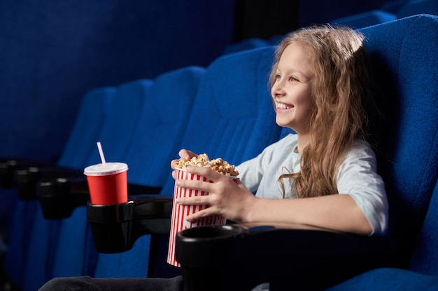 映画館で面白いコメディーで笑って幸せな女の子の側面図