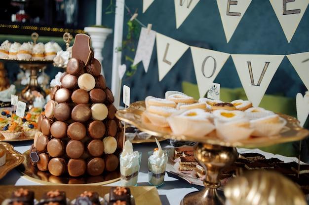 お菓子のあるテーブル、オレンジ色の蝶で飾られたピラミッド、キャンディーバー
