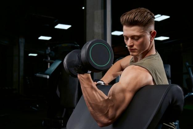 Спортсмен тренирует бицепс с гантелями.