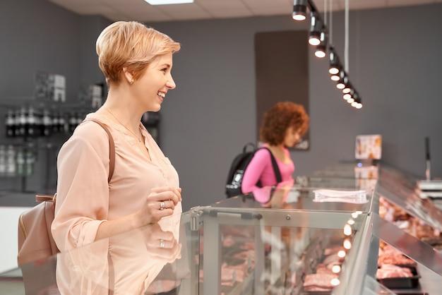 ガラスのカウンターの後ろで肉を選ぶ女性。